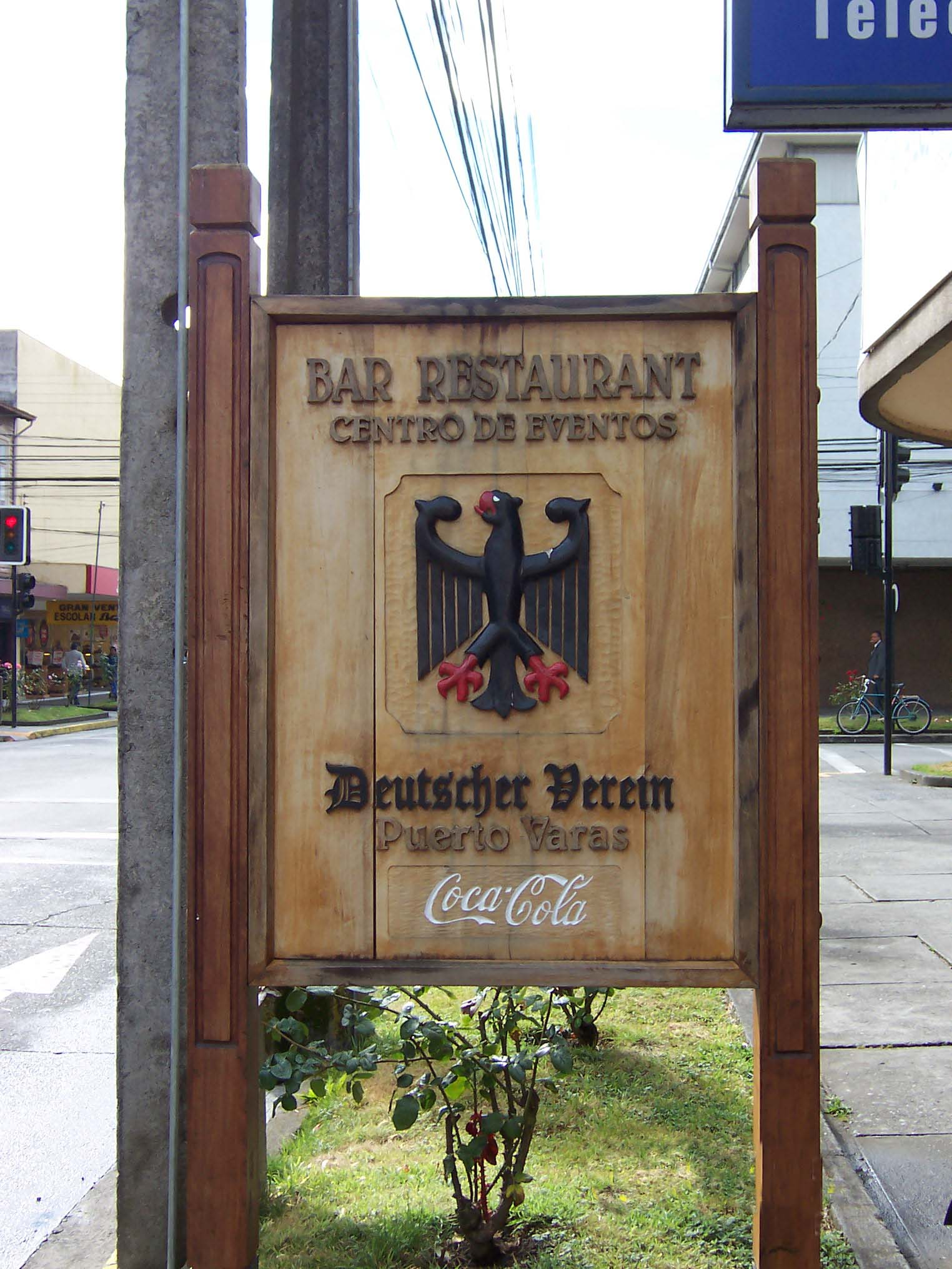 Wood-carved street sign beckoning diners to the Club Alemán's bar and restaurant. The German eagle greets Atlanta's global beverage in South America